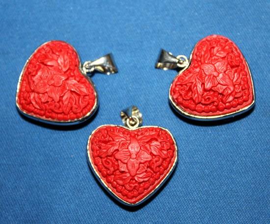 Pendiente de corazón tallado en piedra de Cinnabar.